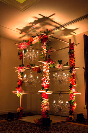 A grid structure with hanging chandeliers and exotic flowers at a wedding in Bengaluru