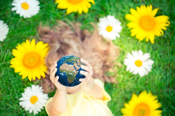 Child holding 3d planet in hands against