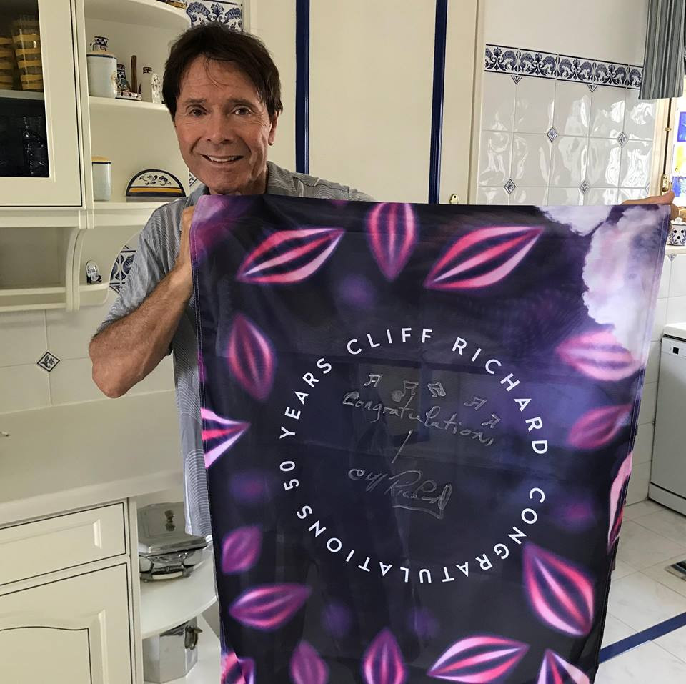 Sir Cliff Richard with the Flying The Flag charity flag
