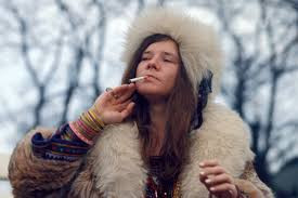 Janis Joplin in a fur coat and hat smoking a cigarette