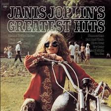 Greatest Hits album cover featuring Janis Joplin on a motorcycle wearing sunglasses and smiling