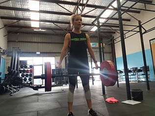 Female athlete performing trap bar deadlift in strength workout.