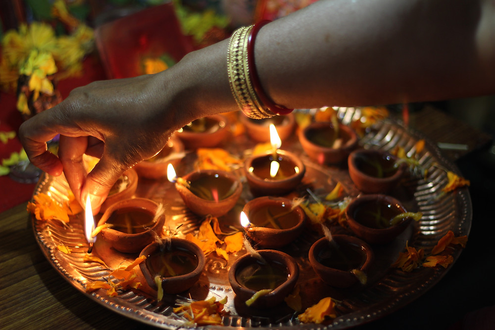 Lighting Diya during Diwali Puja. Articles on Meditation, Mindfulness, Nonduality and Integrated Healthcare written by Dr. Vikas Pandey