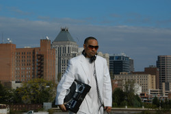 DJ PRECISE(freddie fontaine)-pic in white suit city in background holding Numark