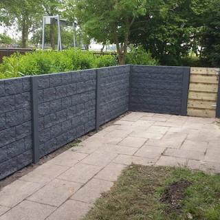 betonnen schutting met houten poort