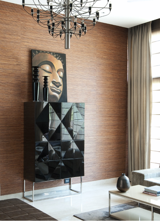 Tall cabinet with Art placed on top. Wallpaper in the background. Contemporary chandelier.