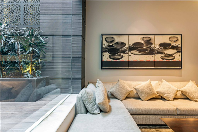 Art above Sofa.Sepia tones in a neutral themed home. Greenery in the patio balances the lack of color.