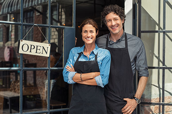 Two cheerful small business owners smiling and looking at camera while standing at entrance door with open sign board.