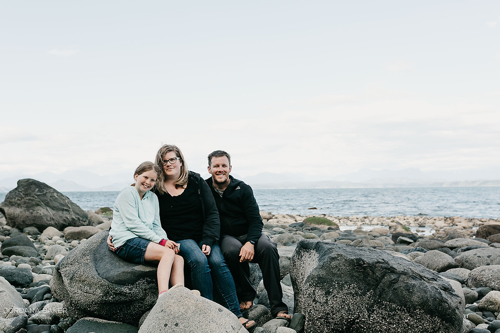 Family sitting on a rock by the ocean