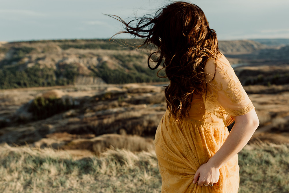 Pregnant woman in yellow dress holding the side as she walks along Dry Island Buffalo Jump