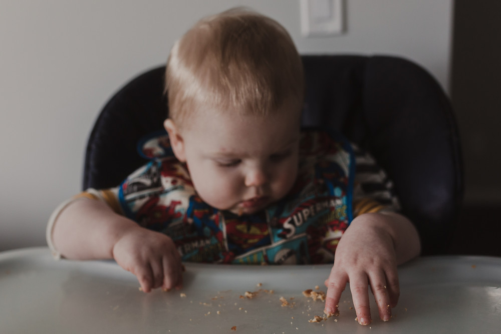 Blonde boy sitting in high chair squishing crumbs with his hands