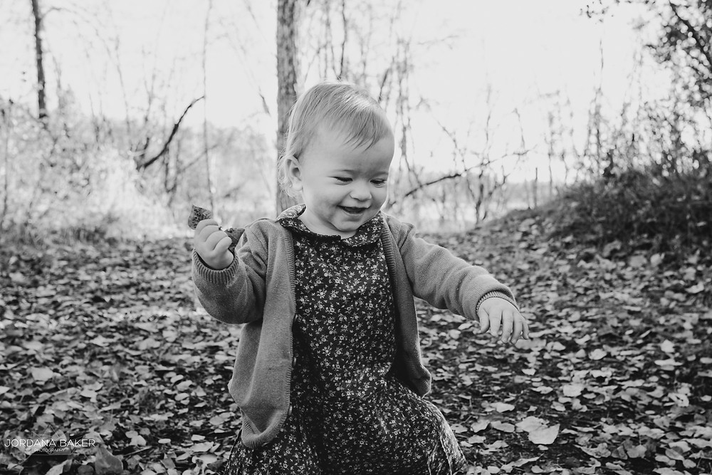Small girl in leaves during family photograph by Jordana Baker Photography