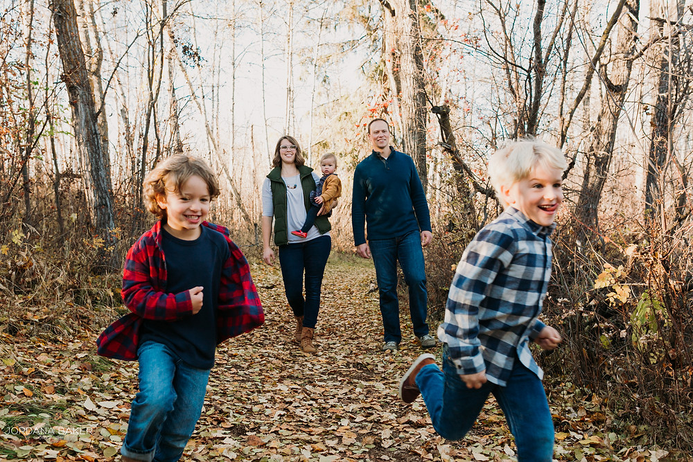 kids running in front of their parents for fall family photographs in Airdrie by Jordana Baker Photography