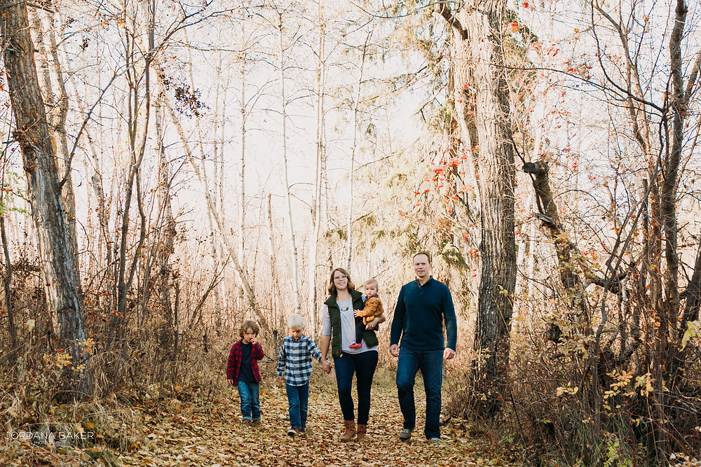Family walkind down path hand in hand for family photographs with Jordana Baker Photography in Lacombe
