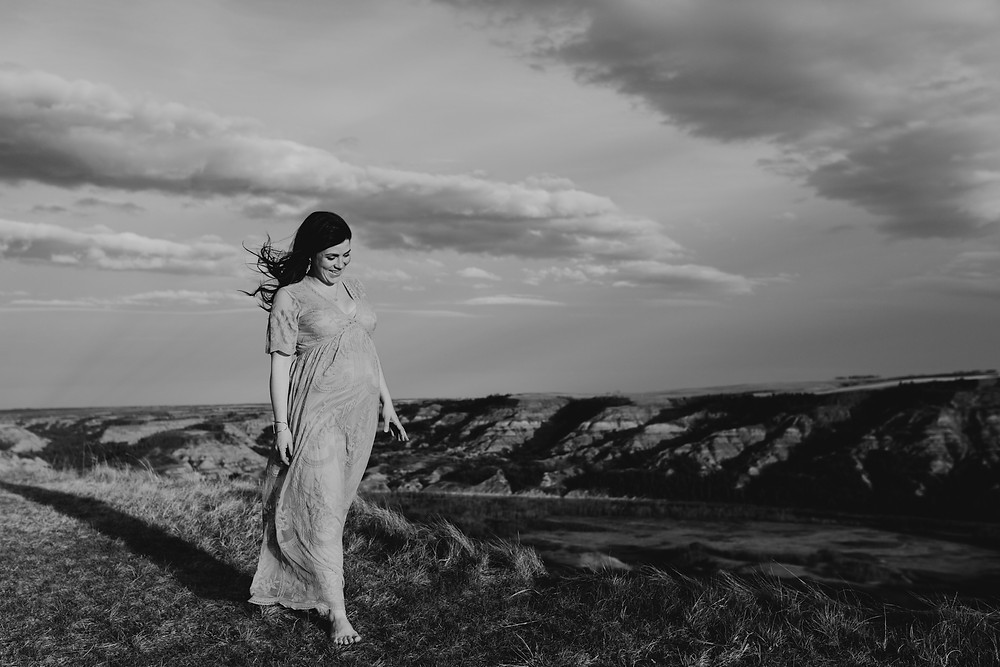 Pregnant woman in long dress walking at Dry Island Buffalo Jump smiling with wind in her hair.
