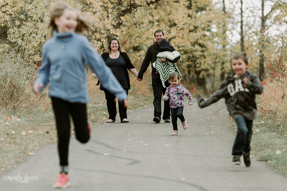 Couple walking down a path holding their child while the siblings run infront laughing on a fall day