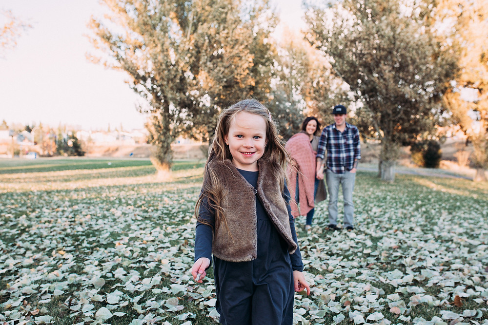 A girl in the foreground of her family on a fall evening.  Jordana Baker Photography