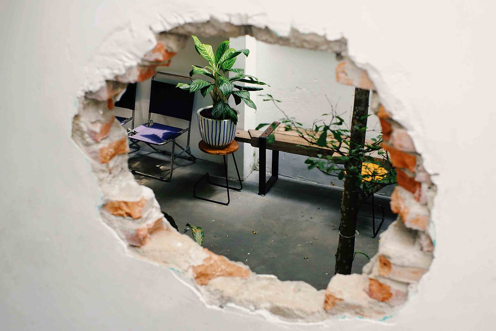 Hole in a white wall exposing bricks and showing a waiting room