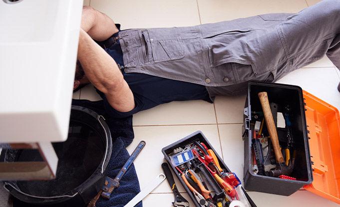 Tradesman working under a sink