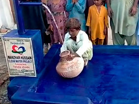 Young boy getting water from a well.
