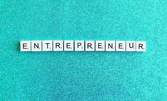 the word entrepreneur spelt out in scrabble letters on glittery blue background