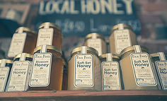 Jars of honey stack on a shelf