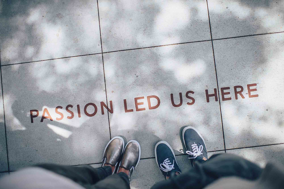 Looking down at a Passion Led Us Here sign on a tiled floor