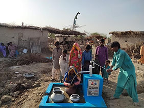 People gathered around a new water well in Pakistan