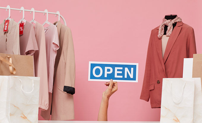 Clothing shop with assistant holding up an open sign.