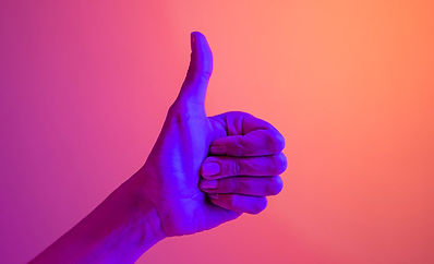 Thumb up on pink background illuminated by purple light