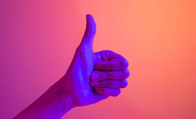 Thumb up on pink background illuminated by purple light