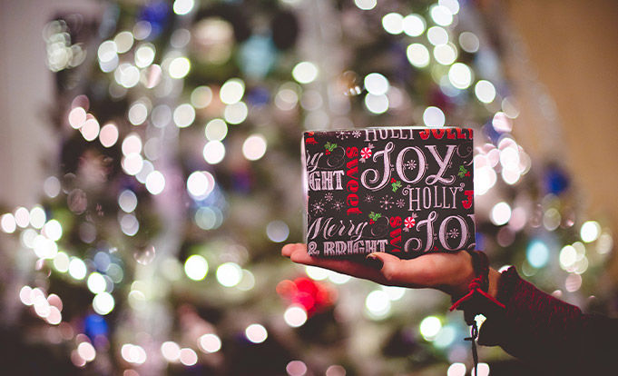 A person holding a Christmas Present in font of a blurred out Christmas tree.