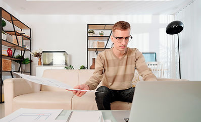 Man working on laptop and holding documents working from home