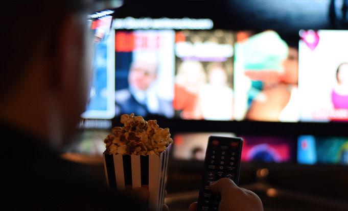 Man watching streaming service eating popcorn