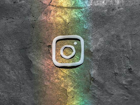 Instagram logo upon a steal background with a rainbow colour running through the middle, top to bottom