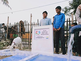 Two young Muslim boys standing over completed water well donated by Purpose of Life Charity