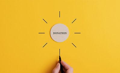 Donate word written on a little wooden circle.