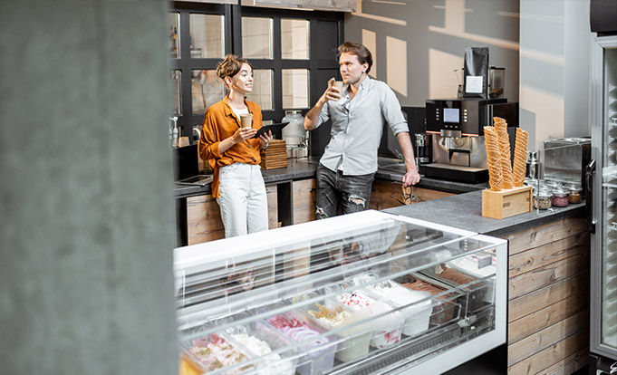 Man and woman having a drink waiting to open an ice cream shop