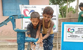 Two young people collecting water from a newly built water well in India