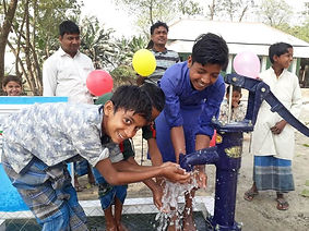 Young men happy with new water well installed by Purpose of Life