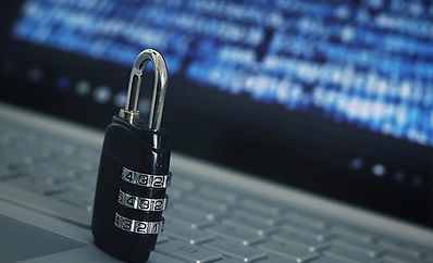 Padlock in front of laptop computer showing data on the screen.