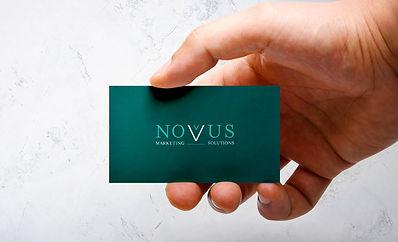 Man holding Novus Marketing Solutions Business Card