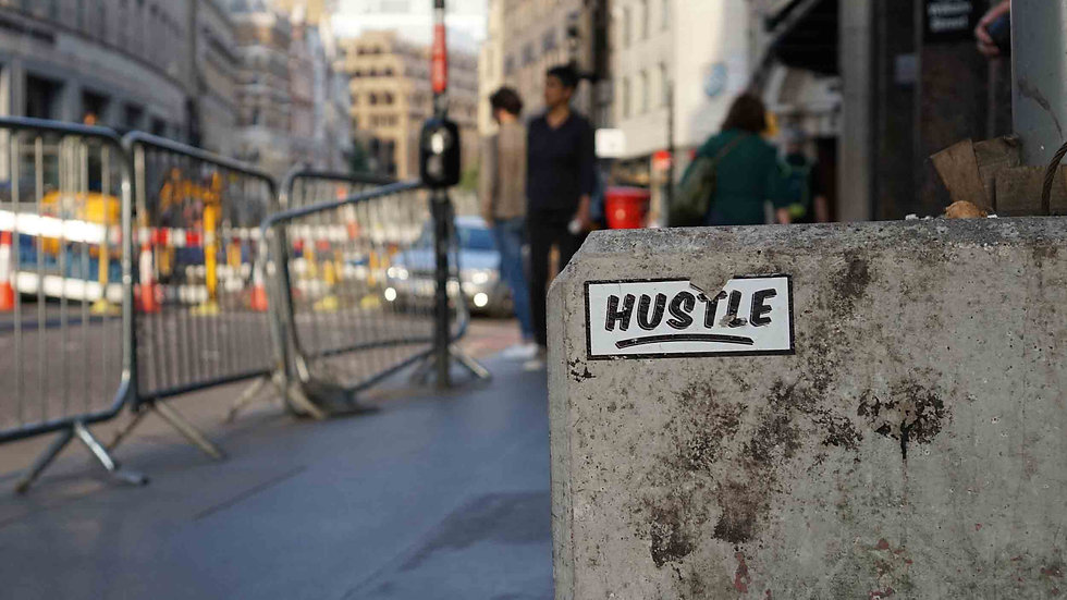 The word hustle on a sticker on a concrete block
