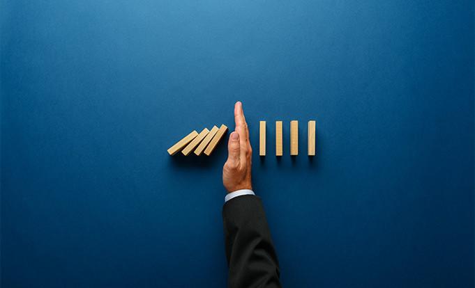 Hand on blue background showing risk management