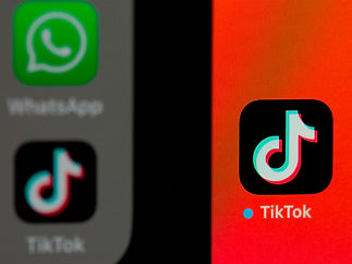 tiktok icons shown on a mobile phone up close and a desktop