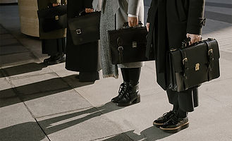 4 people in a row holding briefcases wearing business attire.