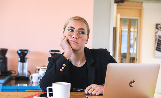 Woman at laptop trying to find her focus to work