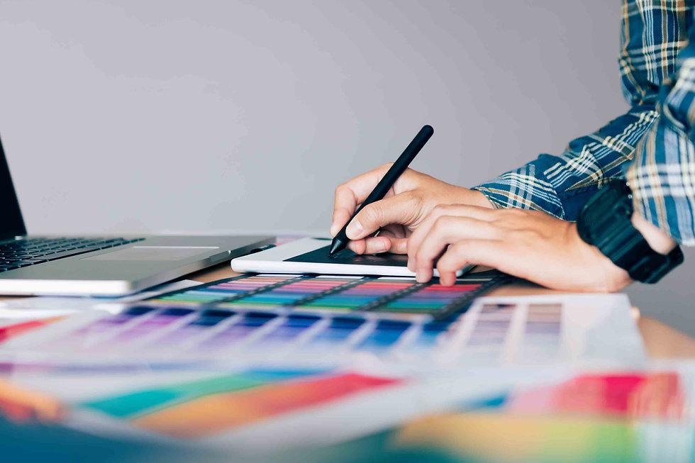 Hands working as a freelance designer on a desk
