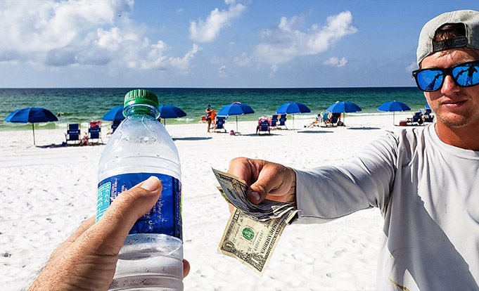 Man selling water to someone on a very busy sunny beach