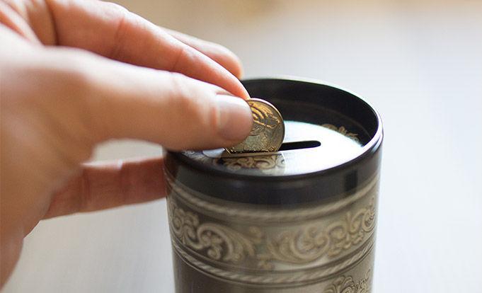 Saving money in a tin.